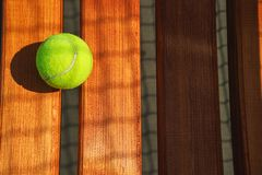 Tennis ball on the bench. stock image
