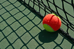 Tennis ball besides the net. Yellow-red balls on a green tennis court Stock Photos