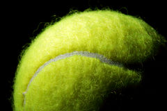 Tennis ball on a black background. Tennis ball against a black background with moody lighting Royalty Free Stock Photography