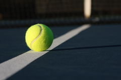 Tennis ball on a blue court. Tennis ball on the court line of a blue court Stock Photography