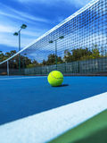 Tennis Ball on Blue Court, Doubles Sideline and Net. Close-up low angle perspective of tennis ball on blue tennis forecourt surface with net oil background. Blue Royalty Free Stock Photography