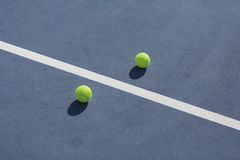 Tennis ball on blue and green hard court Royalty Free Stock Image