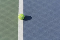 Tennis ball on blue and green hard court Royalty Free Stock Photo