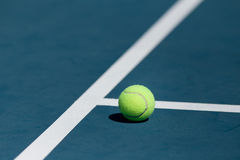 Tennis ball. On blue hard court inside of line Royalty Free Stock Image