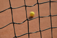 Tennis ball blurred photo through the tennis net Stock Image