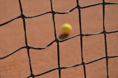 Tennis ball blurred photo through the tennis net Stock Image