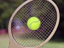 Tennis Ball Breaks Through Racquet Strings. A tennis ball exploding through the strings of a tennis racquet Stock Images