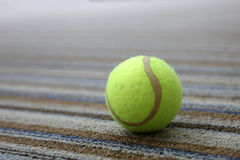 Tennis ball on the carpet. A tennis ball on the carpet Stock Photo