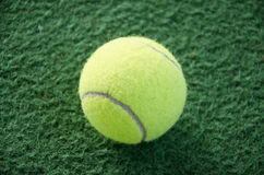 Tennis ball. On a carpet indoor court Stock Photo