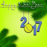 Tennis ball and 2017 on a Christmas tree branch. Happy New Year and numbers 2017 and tennis ball as a Christmas decorations hanging on a Christmas tree branch Royalty Free Stock Photo