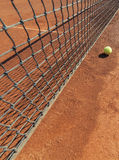 Tennis ball on clay court Stock Photos