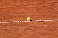 Tennis ball on a clay court Stock Photos