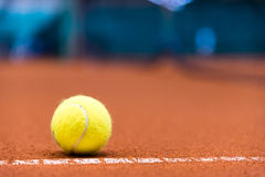 Tennis ball on a clay court Stock Photos