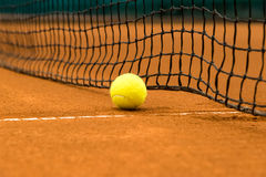 Tennis ball on a clay court Royalty Free Stock Image