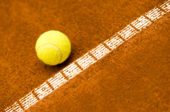 Tennis ball on a clay court Stock Photography