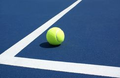 Tennis Ball on blue tennis court Royalty Free Stock Images