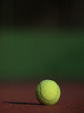 Tennis ball on the court. Close-up view of a tennis ball on a sunlit tennis court  (late afternoon -> warm light Royalty Free Stock Images