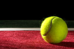 Tennis Ball on a Court. Tennis ball on soft indoor court surface Royalty Free Stock Photography