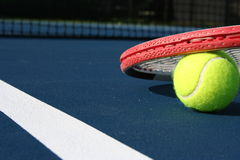 Tennis Ball on Court. A tennis ball and racket on a blue court Royalty Free Stock Images