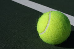 Tennis ball on the court. Near the court line Royalty Free Stock Photography