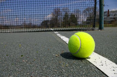 Tennis ball on court. A tennis ball on the line of a court stock photography