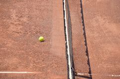Tennis ball on the court. High angle view of tennis ball on the court field next to the net after a workout Stock Image