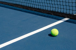 Tennis ball on court. Image of a tennis ball on the court with net and line Stock Images