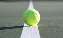Tennis ball on court line. Optical yellow tennis ball sitting on a white boundary line of a hard court, casting a long shadow...taken from ground level, the line Stock Photos