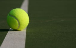 Tennis ball on the court line. Tennis ball on the court with room for copyspace Stock Photography