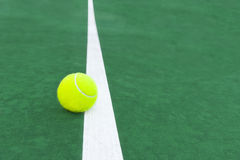 Tennis ball on court line Royalty Free Stock Image