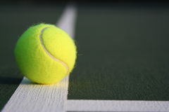 Tennis ball on court line off center Royalty Free Stock Image