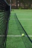 Tennis ball on a court neat net. Yellow tennis ball on a green court neat net Stock Photography