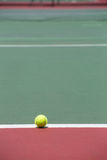 Tennis Ball on the Court. With the Net in the background Stock Photo
