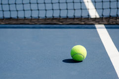 Tennis ball on court with net Stock Photo