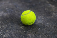 Tennis ball on the dirty ground Royalty Free Stock Photography