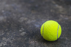 Tennis ball on the dirty ground Royalty Free Stock Photo