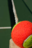 Tennis ball on the edge of the net. Yellow-red balls on a green tennis court Royalty Free Stock Photo