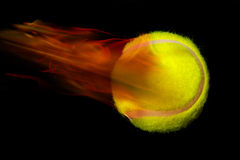 Tennis ball on fire. Montage of yellow tennis ball on fire with motion effect, isolated on black background Royalty Free Stock Photography
