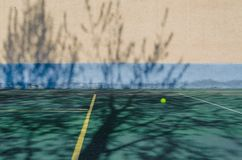 A tennis ball flying in the air. Tennis ball, tennis court, ball over the tennis court royalty free stock photo