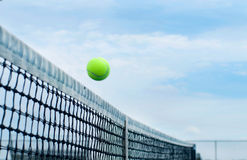 Tennis ball flying over middle net court on background blue sky. Tennis concept stock photography