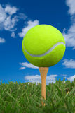 Tennis ball on golf tee. From the ground level with grass and cloudy sky stock image