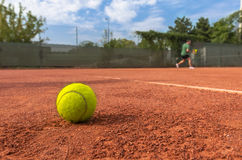 Tennis ball on court. Tennis ball on the court with blurred tennis player in the background royalty free stock image