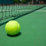 Tennis ball on green court Stock Photos