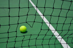 Tennis ball on green court Royalty Free Stock Image