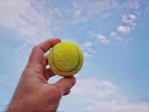 Tennis ball in hand against blue sky royalty free stock photo