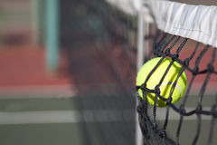 Tennis ball hitting the net on a court Stock Photography