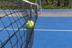 Tennis ball hitting on the net. Yellow tennis ball flew into the net on the blue court stock photo