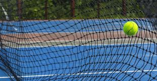 Tennis ball hitting on the net. Yellow tennis ball flew into the net on the blue court stock photos