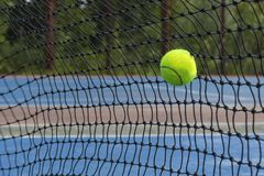 Tennis ball hitting on the net. Yellow tennis ball flew into the net on the blue court royalty free stock images