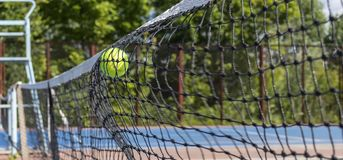 Tennis ball hitting on the net. Yellow tennis ball flew into the net on the blue court royalty free stock photography